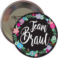Schwarzer Team Braut JGA-Button mit Blumenkranz-Motiv