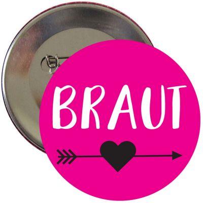Pinkfarbener JGA Ansteck-Button mit Braut-Aufschrift und Herz mit Pfeil-Motiv