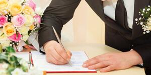 Bräutigam unterschreibt auf dem Standesamt